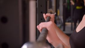 Closeup shoot of young attractive athlete female hands getting ready to lift weights in the gym indoors.  stock video footage