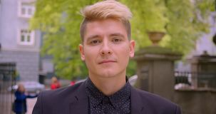 Closeup shoot of young attractive caucasian blonde man smiling happily looking at camera in the park outdoors.  stock video
