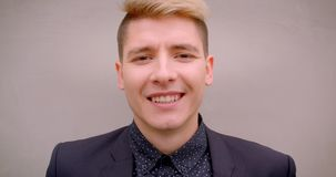 Closeup shoot of young attractive caucasian blonde man smiling happily looking at camera with the wall on the background.  stock video