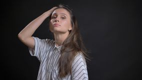 Closeup shoot of young attractive caucasian female fashion model tossing hair and posing in front of the camera with. Confidence looking straight stock photo