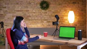 Closeup shoot of young attractive caucasian female video blogger streaming live and talking cheerfully on camera showing stock footage
