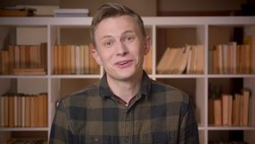 Closeup shoot of young attractive caucasian male student being excited and surprised looking at camera in the college stock video footage