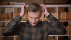 Closeup shoot of young attractive caucasian male student having a headache looking at camera in the college library.  stock video