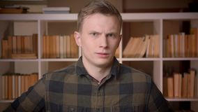 Closeup shoot of young attractive caucasian male student waving his head saying no being angry looking at camera in the stock video footage