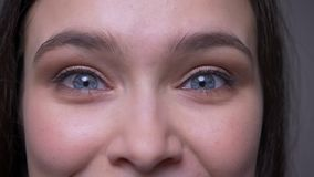 Closeup shoot of young attractive female face with blue sparkling eyes looking at camera with smiling facial expression.  stock footage