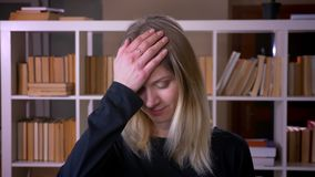 Closeup shoot of young attractive female student making a face palm being annoyed looking at camera indoors in the. University library stock video footage