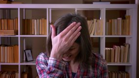 Closeup shoot of young attractive female student making a face palm being frustrated and exhausted looking at camera in. The library indoors stock footage