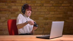 Closeup shoot of young attractive hipster female video blogger playing video games using the game console on the laptop royalty free stock photos