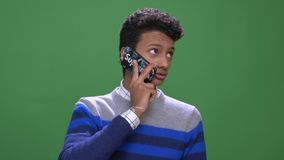 Closeup shoot of young attractive indian male having a phone call with background isolated on green stock video footage