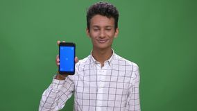 Closeup shoot of young attractive indian male using the phone and showing blue screen to camera with background isolated stock video