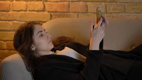 Closeup shoot of young beautiful caucasian brunette female lying on the couch and using the phone indoors in a cozy. Apartment royalty free stock photo