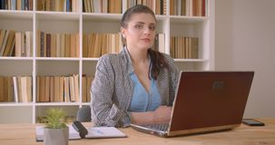 Closeup shoot of young caucasian businesswoman using the laptop looking at camera smiling confidently in the library. Office indoors stock video footage