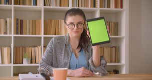 Closeup shoot of young caucasian businesswoman using the tablet and showing green screen to camera in the library office. Indoors stock footage