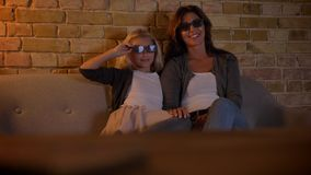 Closeup shoot of young caucasian female and her small daughter watching an action movie TV in 3D glasses at home.  stock video footage