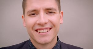 Closeup shoot of young cheerful caucasian blonde man smiling happily looking at camera with the wall on the background.  stock video footage
