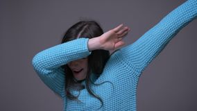 Closeup shoot of young cool brunette female dabbing with confidence looking at camera with background isolated on gray stock video footage