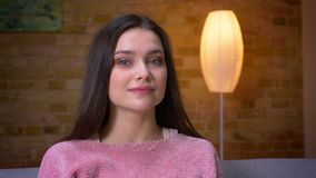 Closeup shoot of young cute brunette caucasian girl looking at camera and smiling happily sitting on the couch in a cozy