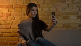Closeup shoot of young cute caucasian female taking selfies on the phone while resting on the sofa at cozy home indoors royalty free stock image