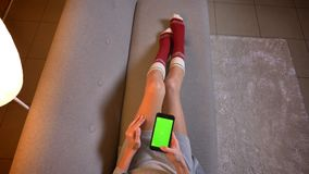 Closeup shoot of young cute female texting on the phone with green chroma screen. Womans thighs in cute christmas-themed. Socks on the cozy sofa stock video footage