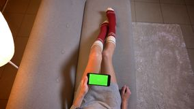 Closeup shoot of young cute female using the phone with green chroma screen. Womans thighs in cute christmas-themed. Socks on the cozy sofa stock video