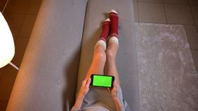 Closeup shoot of young cute female using and turning the phone with green chroma screen. Womans thighs in cute christmas. Themed socks on the cozy sofa stock footage