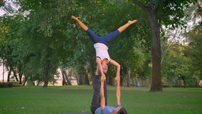 Closeup shoot of young female and male training acroyoga star pose in the park. Woman being raised up on mans toes and. Spreading her legs stock video