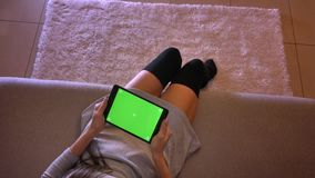 Closeup shoot of young female teenager holding the tablet with green screen horizontally. Girls legs in cute socks. Sitting on the sofa indoors stock footage