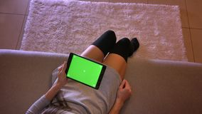 Closeup shoot of young female teenager playing video on the tablet with green screen vertically. Girls legs in cute. Socks sitting on the sofa indoors stock video footage