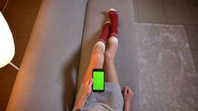 Closeup shoot of young female watching a movie on the phone with green chroma screen. Womans thighs in cute christmas. Socks on the cozy sofa stock video footage