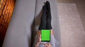 Closeup shoot of young girls legs in cute socks on the sofa indoors. Tender female holding the tablet with green screen. Horizontally and scrolling stock footage
