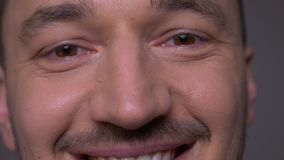 Closeup shoot of young handsome caucasian male face with eyes looking at camera with smiling expression with background. Isolated on gray stock video footage