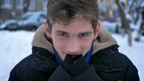 Closeup shoot of young handsome caucasian male freezing and warming hands smiling in a winter coat outdoors in a snowy. Day stock footage