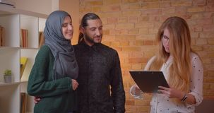 Closeup shoot of young happy muslim couple discussing with a realter a new apartment hugging cheerfully indoors stock video