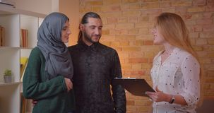Closeup shoot of young happy muslim couple discussing with a realter a new apartment smiling cheerfully indoors stock video footage