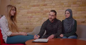 Closeup shoot of young happy muslim couple signing a deal with a realter on buying a new apartment and receiving keys. Sitting on the couch stock video