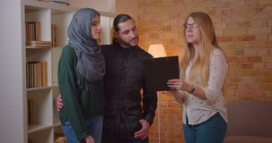Closeup shoot of young happy muslim couple talking to realter in a newly bought apartment hugging cheerfully indoors stock video
