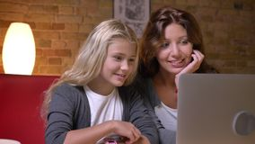 Closeup shoot of young mother and her small pretty daughter using the laptop together and talking with excitement at stock video
