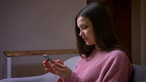 Closeup shoot of young pretty brunette caucasian female texting on the phone and laughing sitting on the couch in a cozy