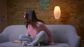 Closeup shoot of young pretty brunette caucasian female using the phone and smiling with excitement sitting on the couch. In a cozy apartment indoors stock video footage