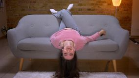 Closeup shoot of young pretty brunette caucasian female watching TV with excitement and lying upside down on the couch. In a cozy apartment indoors stock footage