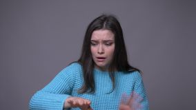 Closeup shoot of young pretty brunette female mime gesturing and imaginary butterfly with background isolated on gray stock video