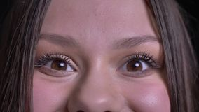 Closeup shoot of young pretty caucasian brunette female face with brown eyes looking straight at camera with excitement.  stock video