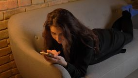 Closeup shoot of young pretty caucasian brunette female lying on the couch and browsing on the phone indoors at cozy. Home stock photos