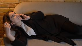 Closeup shoot of young pretty caucasian brunette female lying on the couch and calling on the phone indoors in a cozy. Apartment stock photography