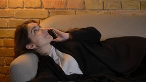 Closeup shoot of young pretty caucasian brunette female lying on the couch and having casual conversation on the phone. Indoors in a cozy apartment royalty free stock photography