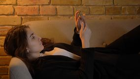 Closeup shoot of young pretty caucasian brunette female lying on the couch and using the phone indoors in a cozy. Apartment royalty free stock photos