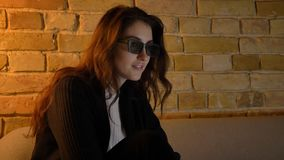 Closeup shoot of young pretty caucasian female being relaxed and watching 3D movie on TV while sitting on the couch. Indoors in a cozy apartment stock photography