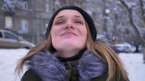 Closeup shoot of young pretty caucasian female with brunette hair being happy and looking around her with excitement in. A snowy winter day outdoors stock video footage