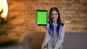 Closeup shoot of young pretty caucasian female with dyed hair using the tablet and showing a green screen to camera
