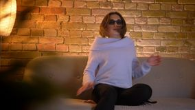Closeup shoot of young pretty caucasian female watching a 3D action movie on TV in glasses getting startled and excited. Sitting on the couch indoors stock video footage